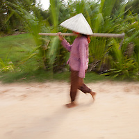 A farmer near the Vietnam border in Cambodia wears a hat typical of the area