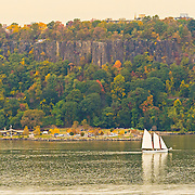 On a fall day, this sailboat was going north up the Hudson river past the Palisades in their early autumn colors