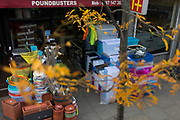 Autumn leaves and in the background, the displayed stock of a Poundbuster shop on the Walworth Road, on 17th October 2017, in south London, England.