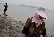 """Portrait of a woman with her head covered at the open """"Mysterious Sea Road"""" in Hoedong shore (Jindo island). Jindo is the 3rd biggest island in South Korea located in the South-West end of the country and famous for the """"Mysterious Sea Route"""" or """"Moses Miracle"""". Every spring thousands flock to the shores of Jindo to walk the mysterious route that stretches roughly three kilometers from Hoedong to the distant island of Modo. Materializing from the rise and fall of the tides, the divide can reach as wide as forty meters."""