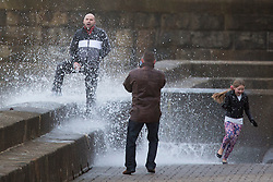 """© Licensed to London News Pictures. 09/11/2015. Bridlington, UK. FRAME 7 OF 9. A man poses for a photograph on the sea defences at the sea side town of Bridlington & gets caught out by a huge wave. The Yorkshire region was hit by severe gales this afternoon with winds up to 60mph. The Met Office warned West Yorkshire to expect gales and locally severe gales over high ground, with some """"very gusty"""" winds to the east of high ground as well.<br /> Photo credit: Andrew McCaren/LNP"""