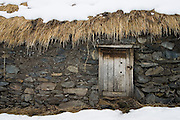 Small hut door in the alpaca herding village of the Q'eros people under snow, Cordillera de Paucartambo, Andes Mountains, Peru.
