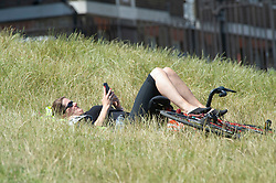 ©Licensed to London News Pictures 22/06/2020<br /> Greenwich, UK. A cyclist having a sunbathe in the long grass. A warm sunny day in Greenwich park, Greenwich, London. The UK to enjoy hot heatwave weather this week with temperatures set to bring the hottest day of the year so far. Photo credit: Grant Falvey/LNP