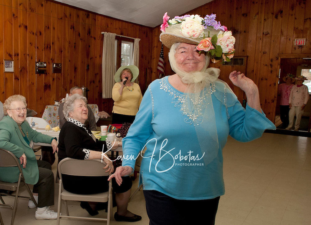 With an introduction from Betty Clark Cecile Campbell works the runway in her flowery Easter bonnet during the Laconia Elder Friendship Club's annual Easter Parade at Leavitt Park Clubhouse Wednesday afternoon.  (Karen Bobotas/for the Laconia Daily Sun)