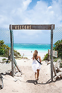 Tulum, Mexico - April 13, 2021: A young woman in Tulum walks onto Playa Las Palmas after parking her bicycle.