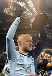 Dec 7, 2013; Kansas City, KS, USA; Sporting KC defender Aurelien Collin (78) hoists the MLS cup after the 2013 MLS Cup against Real Salt Lake at Sporting Park. Mandatory Credit: Denny Medley-USA TODAY Sports