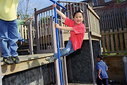 Young boy swinging around metal pole in children's playground laughing,