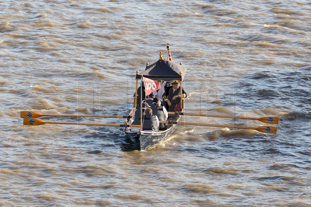 © Licensed to London News Pictures. 11/11/2018. London, UK.  A small traditional vessel with a 100 centenary flag is rowed amongst a flotilla of boats including the Royal barge, QRB Gloriana, the Havengore and traditional boats travel up the River Thames towards the Houses of Parliament in Westminster for a remembrance service, led by the Havengore, as part of Armistice Day centenary events taking place in central London. Big Ben will strike at 11am to mark the start of the two minutes silence and the Havengore will sound her horn to signify the end of the two minutes silence in central London.  Photo credit: Vickie Flores/LNP