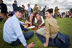 © licensed to London News Pictures. 12/09/2015<br /> Goodwood Revival Weekend, Goodwood, West Sussex. UK.<br /> The Goodwood Revival is the world's largest historic motor racing event. Competitors and enthusiasts dress in period fashions recreating the glorious days of the race circuit.<br /> Pictured Racegoers dressed in period costume at todays event.<br /> <br /> Photo credit : Ian Whittaker/LNP