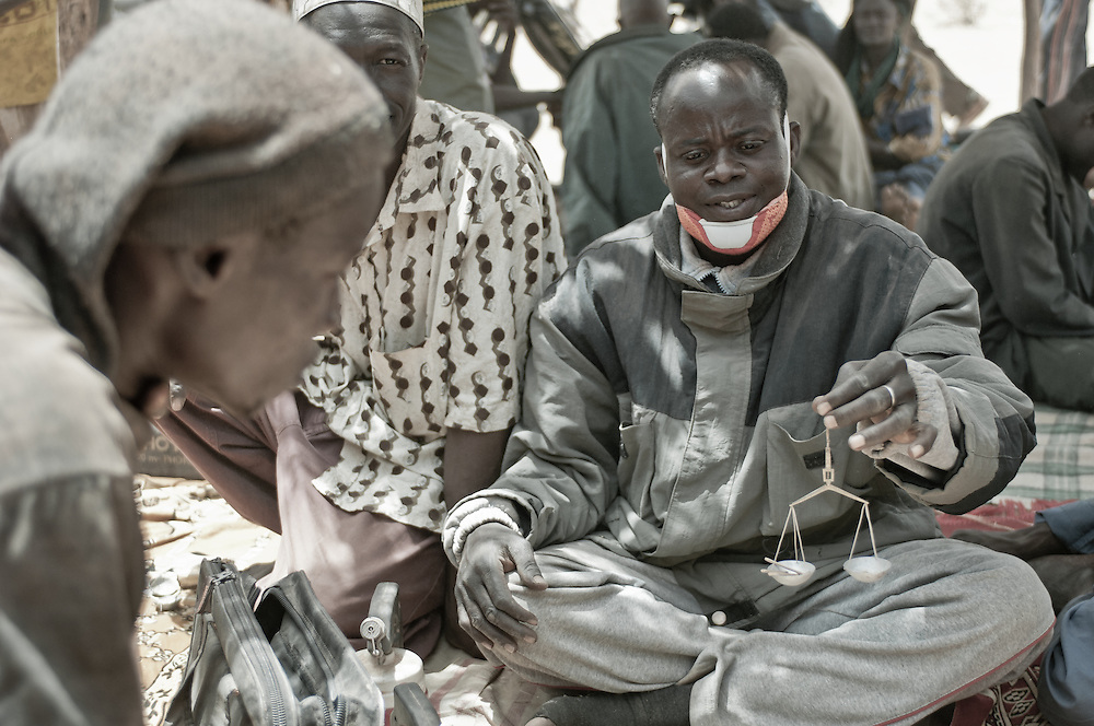 Stock photograph of an African gold buyer weighing the dore at a gold rush camp