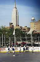 1997:  Kids playing youth roller hockey at Chelsea Piers on a sunny afternoon. The Empire state building NYC landmark in the background. Transparency image scan.