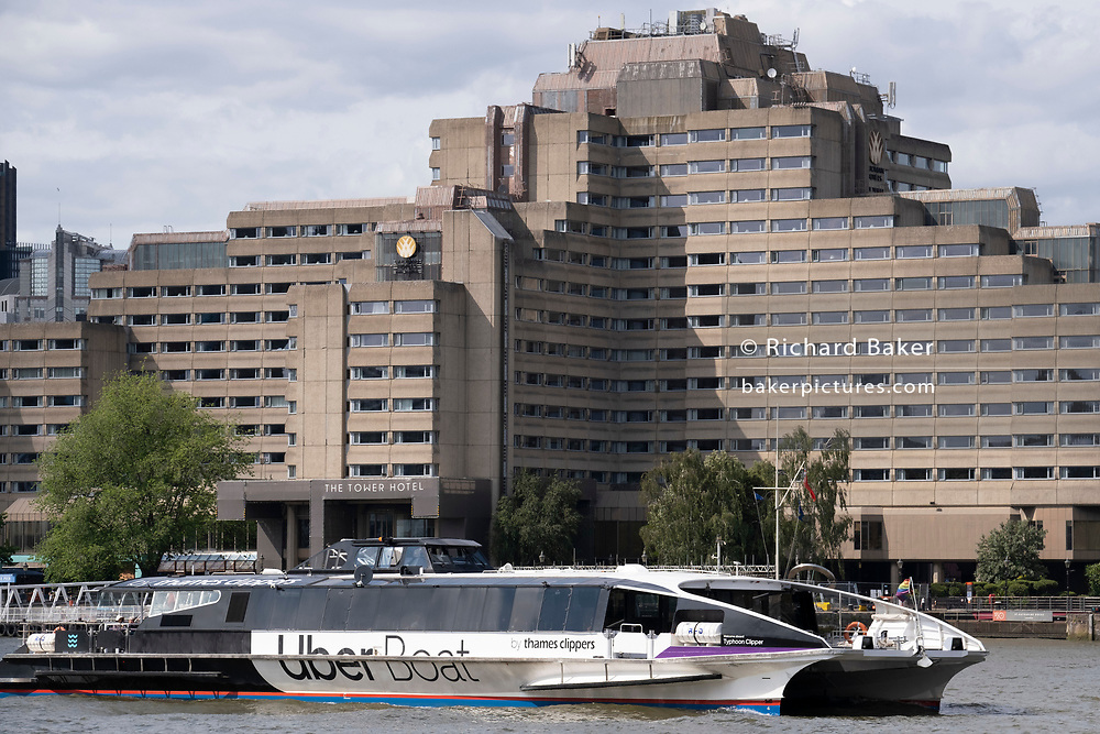 'Typhoon Clipper' which runs part of the Uber Boat taxi service on the Thames river, passes The Tower Hotel near Tower Bridge, on 11th June 2021, in London, England. Thames Clippers operate a fleet of 20 boats on the River Thames, with departures from 23 piers across London from Putney to Woolwich.
