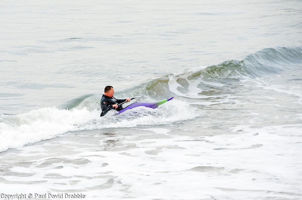 canoeist catches waves towards the beach near Whitby Harbor.September 2010 .Images © Paul David Drabble