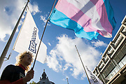 An activist holds a transgender pride flag at a protest by Transgender Action Block and supporters outside the first annual conference of the LGB Alliance at the Queen Elizabeth II Centre on 21st October 2021 in London, United Kingdom. Many LGBT+ activists and advocacy groups are opposed to the LGB Alliance, a government-registered charity, which they consider to be a divisive anti-trans campaign group.