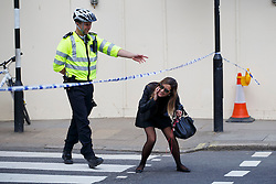 © licensed to London News Pictures. London, UK 14/04/2014. A police officer keeps members of public off the scene in London's Grosvenor Square where part of a building collapsed and killed a man on Monday afternoon of April 14, 2014. Photo credit: Tolga Akmen/LNP