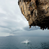 """Thai climber """"deep water soloing"""" without rope, splashes to earth, Poda Island, Krabi, Thailand"""