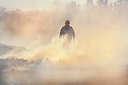Man walking through the smoke created from the springtime burning of the roadside grass verges in Narbonne, France.
