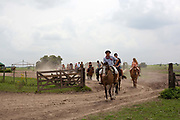 Tourists riding horses with a Gaucho cowby at an Estancia In Lujan, Argentina.