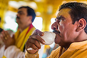 """09 SEPTEMBER 2013 - BANGKOK, THAILAND:  A Hindu priest blows a conch shell horn during Ganesha Chaturthi celebrations at Shiva Temple in Bangkok. Ganesha Chaturthi also known as Vinayaka Chaturthi, is the Hindu festival celebrated on the day of the re-birth of Lord Ganesha, the son of Shiva and Parvati. The festival, also known as Ganeshotsav (""""Festival of Ganesha"""") is observed in the Hindu calendar month of Bhaadrapada. The date usually falls between 19 August and 20 September. The festival lasts for 10 days, ending on Anant Chaturdashi. Ganesha is a widely worshipped Hindu deity and is revered by many Thai Buddhists. Ganesha is widely revered as the remover of obstacles, the patron of arts and sciences and the deva of intellect and wisdom.     PHOTO BY JACK KURTZ"""