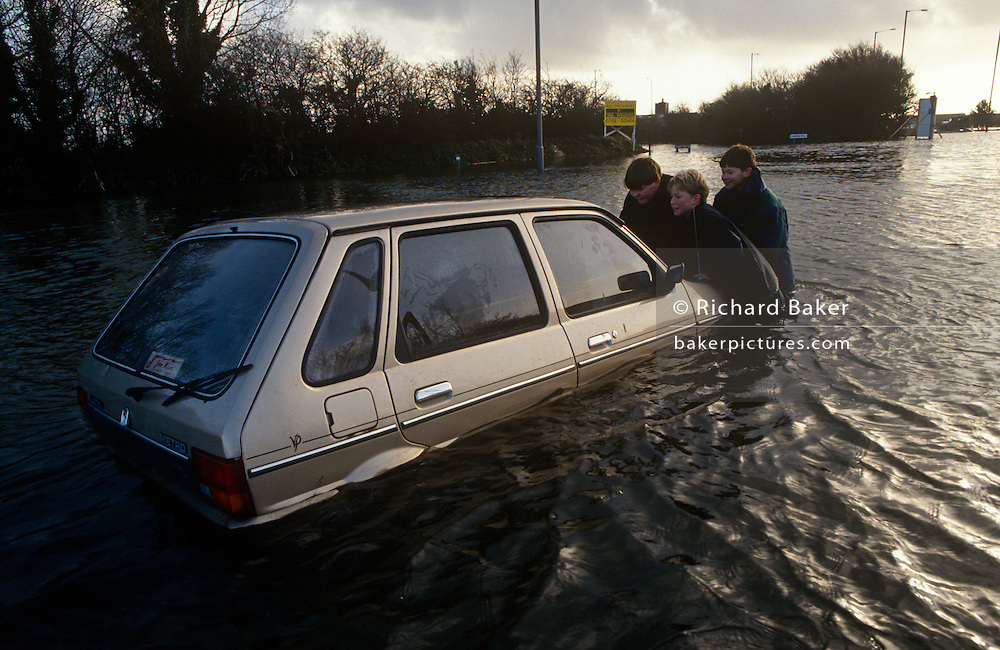 Villagers try to push a stranded car through flood water on the outskirts of Chichester. Heaving on the front bonnet, the people try to rescue the vehicle from rising waters on the outskirts of town. The car has been overcome in a metre of flood water and unable to start on its own. Lavant is a village just north of the city of Chichester. It is made up of two parts, Mid Lavant and East Lavant, and takes its name from the River Lavant which flows from East Dean. This area has been prone to flooding for several years and houses around the rising rivers can be blighted with insurance companies refusing future cover.