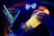 Bartender with a glowing bowtie mixes a martini next to an empty glass with olives.Black light