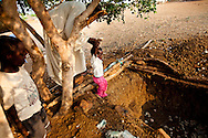 A man stands in the fox hole he buit to protect his family during bombing campaigns. Many families in the Nuba mountains who don't live near caves have built the bunkers in the last week.