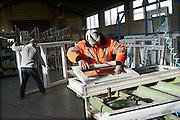 Nederland, Weurt, 31-1-2014Een mederwerker van een bedrijf dat kunststof kozijnen assembleert en installeert is bezig met de montage van een raam.Foto: Flip Franssen/Hollandse Hoogte