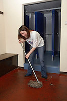 young lady mopping the changing room at a cricket club
