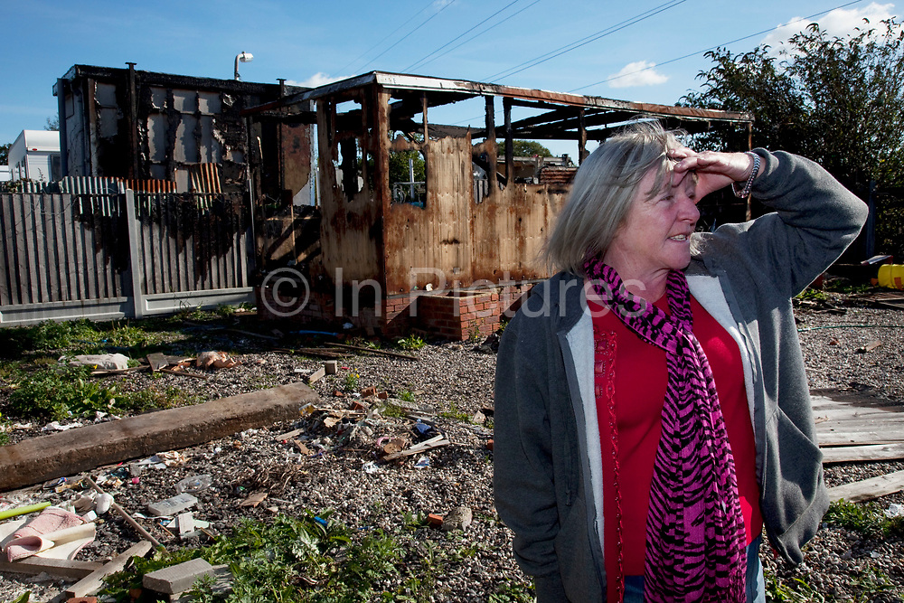 Kathleen McCarthy stands defiantly beside a burned out building at Dale Farm site prior to eviction. Riot police and bailiffs were present on 20th October 2011, as the site was cleared of the last protesters chained to barricades. Dale Farm is part of a Romany Gypsy and Irish Traveller site in Crays Hill, Essex, UK. <br /> <br /> Senior resident Kathleen McCarthy said she now wished to leave, once obstacles are removed, and the majority of residents are expected to join her. Most plan to relocate to Oak Road, on the neighbouring legal site.<br /> <br /> Dale Farm housed over 1,000 people, the largest Traveller concentration in the UK. The whole of the site is owned by residents and is located within the Green Belt. It is in two parts: in one, residents constructed buildings with planning permission to do so; in the other, residents were refused planning permission due to the green belt policy, and built on the site anyway.