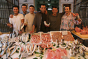 By 8:00 a.m. Giuseppe Manzo and his six co-workers have already spent an hour setting up the fish stand in Palermo, Sicily. In addition to rolling out the red tarps and unfolding the display tables, they must cut and ice the fish, devoting special attention to Sicily's beloved (and increasingly endangered) pesce spada (swordfish), freshly cut chunks of which he arranges around its severed head. Ten hours later, the crew will reverse the process, storing everything for the night. (Supporting image from the project Hungry Planet: What the World Eats.)