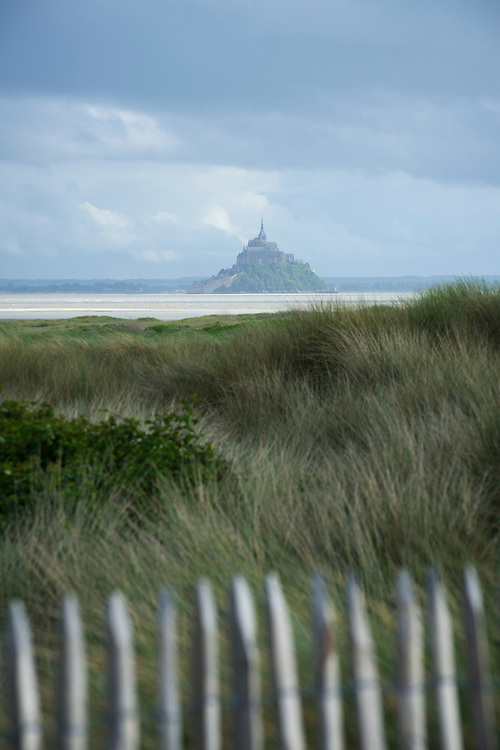 The historic Mont Saint-Michel, topped with its 11th century abbey, seen from the beach in Genêts, France.