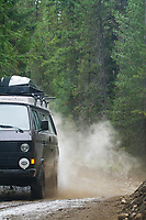 VW van driving really fast through mud puddles near Mt Rainier, WA.