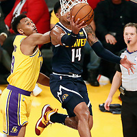 LOS ANGELES, CA - OCT 25: Gary Harris (14) of the Denver Nuggets goes for the reverse layup past Johnathan Williams (19) of the Los Angeles Lakers during a game on October 25, 2018 at the Staples Center in Los Angeles, California.