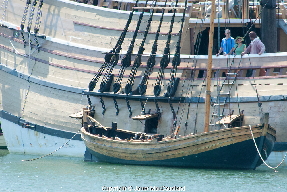A historically correct dory is tied up to the Mayflower ship's replica in Plymouth, Massachusetts. Visitors on the Mayflower overlook the small boat, no doubt pondering months at sea on such cramped quarters.