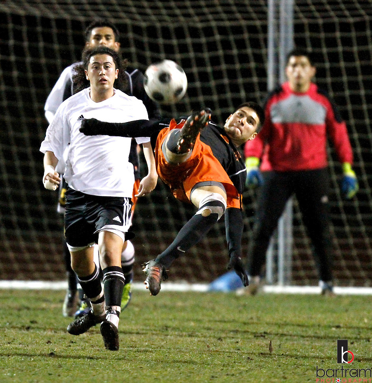 Pittsburg High's Jaime Lopez kicks the ball in front of Antioch High's Luis Diaz during their game at Antioch High School on Tuesday, Feb. 7, 2012. (Photo by Kevin Bartram)