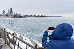 © Licensed to London News Pictures. 31/12/2017. CHICAGO, USA.  A tourist takes in the view at Navy Pier as the waters of Lake Michigan around Chicago have frozen during a period of sub-zero temperatures.  Extremely cold conditions are forecast to continue into the New Year. Photo credit: Stephen Chung/LNP