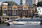 Uber Boats Cyclone Clipper passes Thames riverside residential properties and The Grapes Pub at Limehouse, on 16th September 2021, in London, England. Thames Clippers operate a fleet of 20 boats on the River Thames, with departures from 23 piers across London from Putney to Woolwich.