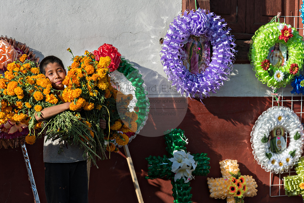 A young boy is hidden in bunches of marigold flowers next to colorful memorial wreaths on sale for the Day of the Dead festival along a street in Santa Clara del Cobre, Michoacan, Mexico.