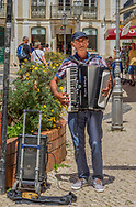 An older gentleman playing the accordian for donations in the Walled City in Lagos, Portugal