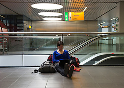 Sarah Pebler, of Madison, Wisconsin, waits for her connecting flight at Schiphol Airport in Amsterdam, the Netherlands, on Tuesday, April 20, 2010. Pebler was stranded in Chicago for four days by the ash cloud from a volcanic eruption in Iceland, before being able to fly to Amsterdam and is waiting for a flight to Nairobi. (Photo © Jock Fistick)