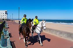 Portobello beach and promenade near Edinburgh during Coronavirus lockdown on 19 April 2020. Empty beach with single yellow bench. Mounted police patrol the promenade.