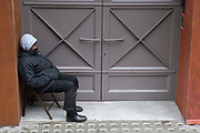 A man sits in a chair at the entrance to a commercial property in Holborn, on 19th February 2021, in London, England.