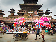 06 AUGUST 2015 - KATHMANDU, NEPAL: Men who sell cotton candy, inflatable toys and papaya wait for customers behind Durbar Square in Kathmandu.      PHOTO BY JACK KURTZ