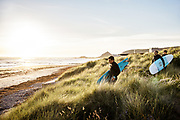 Surfers walking through the grassy sand dunes, holding their surfboards as the sun sets at St Ouen's Bay, Jersey, Channel Islands