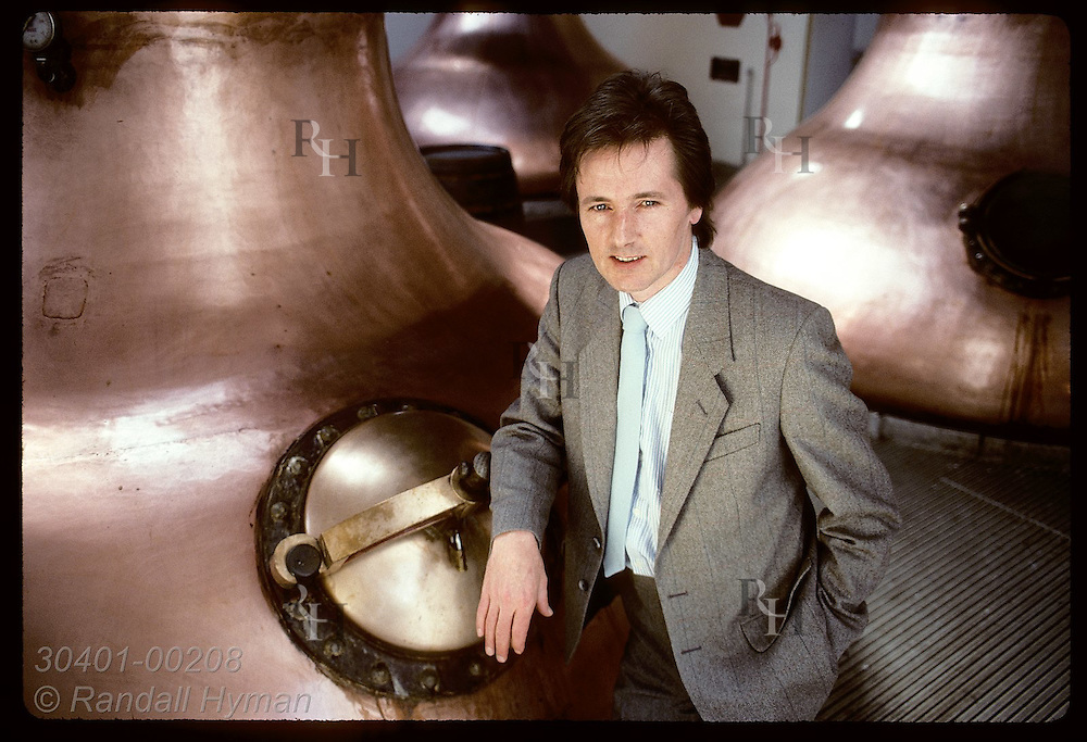 Mike Nicolson, distillery manager, leans on copper wash still at Blair Athol Distillery;Pitlochry Scotland