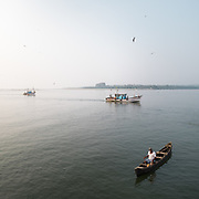 Boats returning at a fishing harbor in Goa.