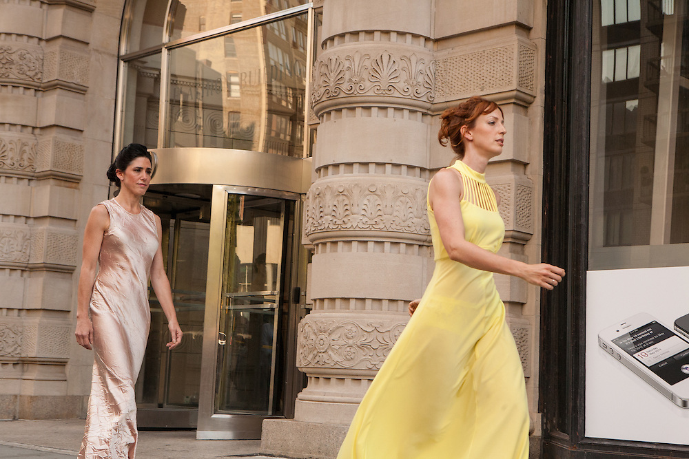 Dancers stroll by the Flatiron Building.