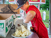 """26 JUNE 2020 - DES MOINES, IOWA: JAX (first name only) uses a drill to slice potatoes to make potato chips at Fair Food Friday in Des Moines. The 2020 Iowa State Fair, like many state fairs in the Midwest, has been cancelled this year because of the COVID-19 (Coronavirus) pandemic. The cancellation of the fair left many small vendors stranded with no income. Some of the fair food vendors in Iowa started """"Fair Food Fridays"""" on a property a few miles south of the State Fairgrounds. People drive up and don't leave their cars while vendors bring them the usual midway fare; corndogs, fried tenderloin sandwiches, turkey legs, deep fried Oreos, lemonaide and smoothies. Fair Food Friday has been very successful. The vendors serve 450-500 people per Friday and during the lunch rush people wait in line in their cars 30 - 45 minutes to place an order.     PHOTO BY JACK KURTZ"""