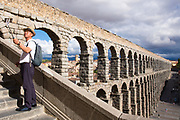Tourist taking selfie photographs with smartphone on selfie stick at famous spectacular Roman aqueduct, Segovia, Spain