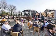 Nederland, Ooij, 17-2-2019Vanwege het mooie weer is het druk op het terras van huiskamercafe oortjeshekken. Op deze warmste 17 februari ooit trekken veel mensen, dagjesmensen, fietsers, er op uit om te genieten van het mooie weer . Het dijkcafe is een toeristische trekpleister voor wandelaars  aan de dijk in de ooijpolder . Foto: Flip Franssen